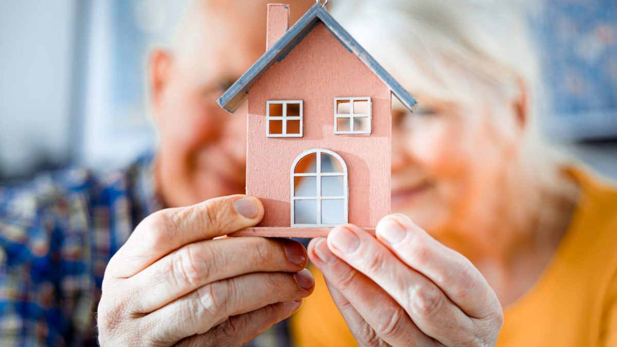 Older Couple holding house cutout